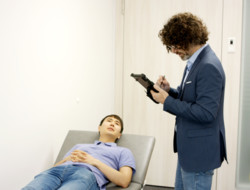 Healthcare Emergency Room Scenario: Doctor is taking notes on his Tablet