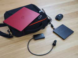 Notebook on top of Prestige Case with mouse, car adapter, and DVD writer