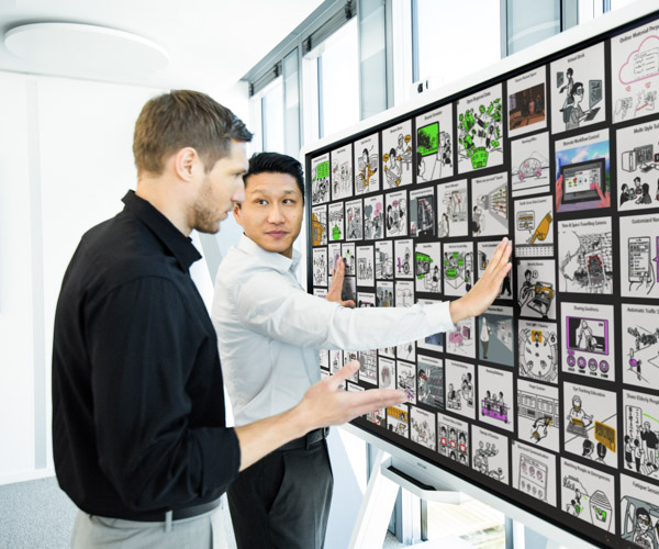 Two office workers discuss a large wall display of images