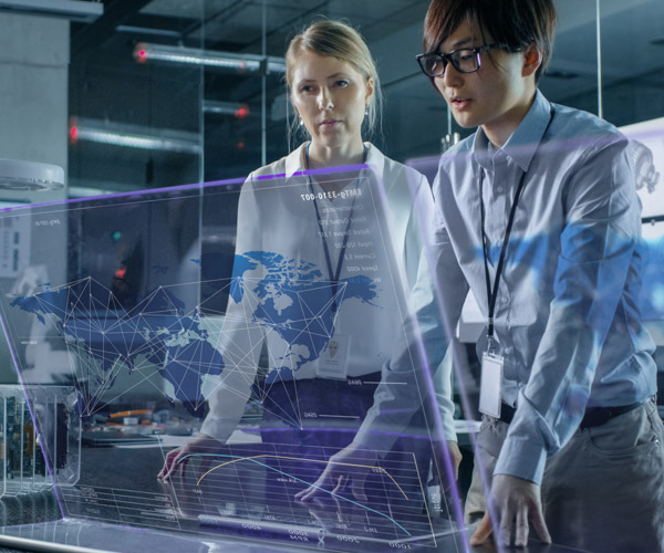 A woman and a man study a futuristic glass map