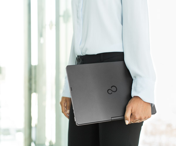 A man carrying a laptop computer by his side