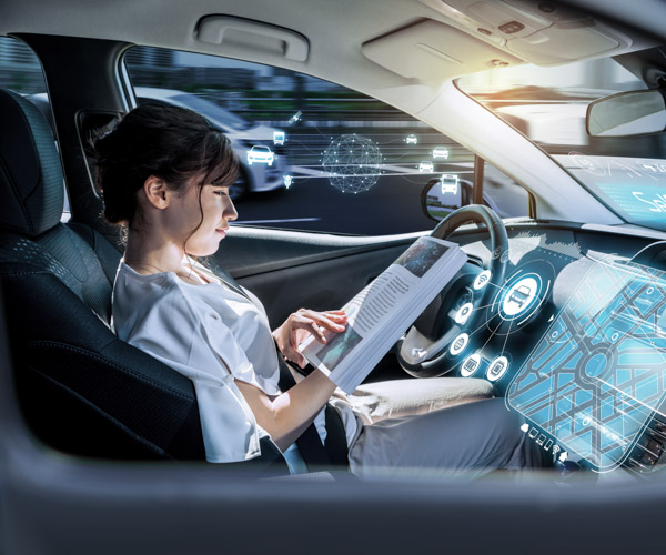 A woman is relaxing, reading a book, in a self-driving car