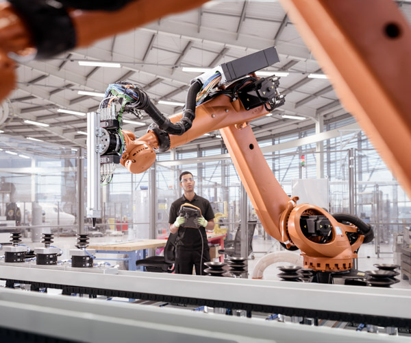 A worker operates large robotic arms in a factory