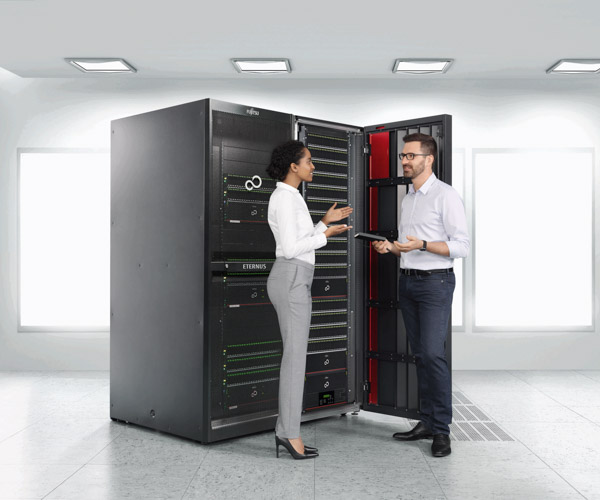 A woman and a man have a discussion in front of an open server rack