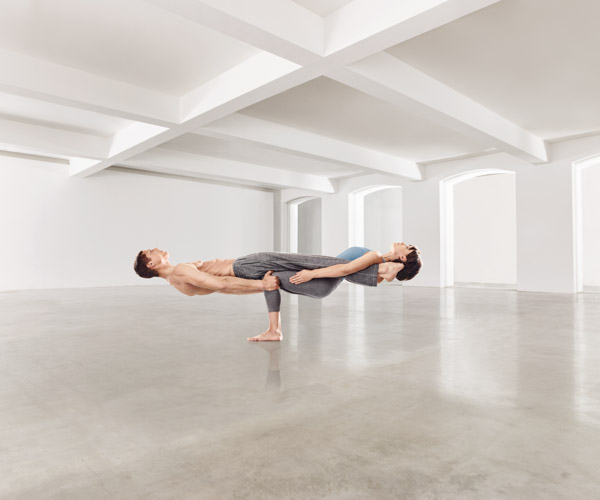 A man and woman doing advanced yoga poses in an empty white room