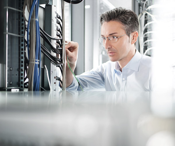 A technician intently studies some network cabling